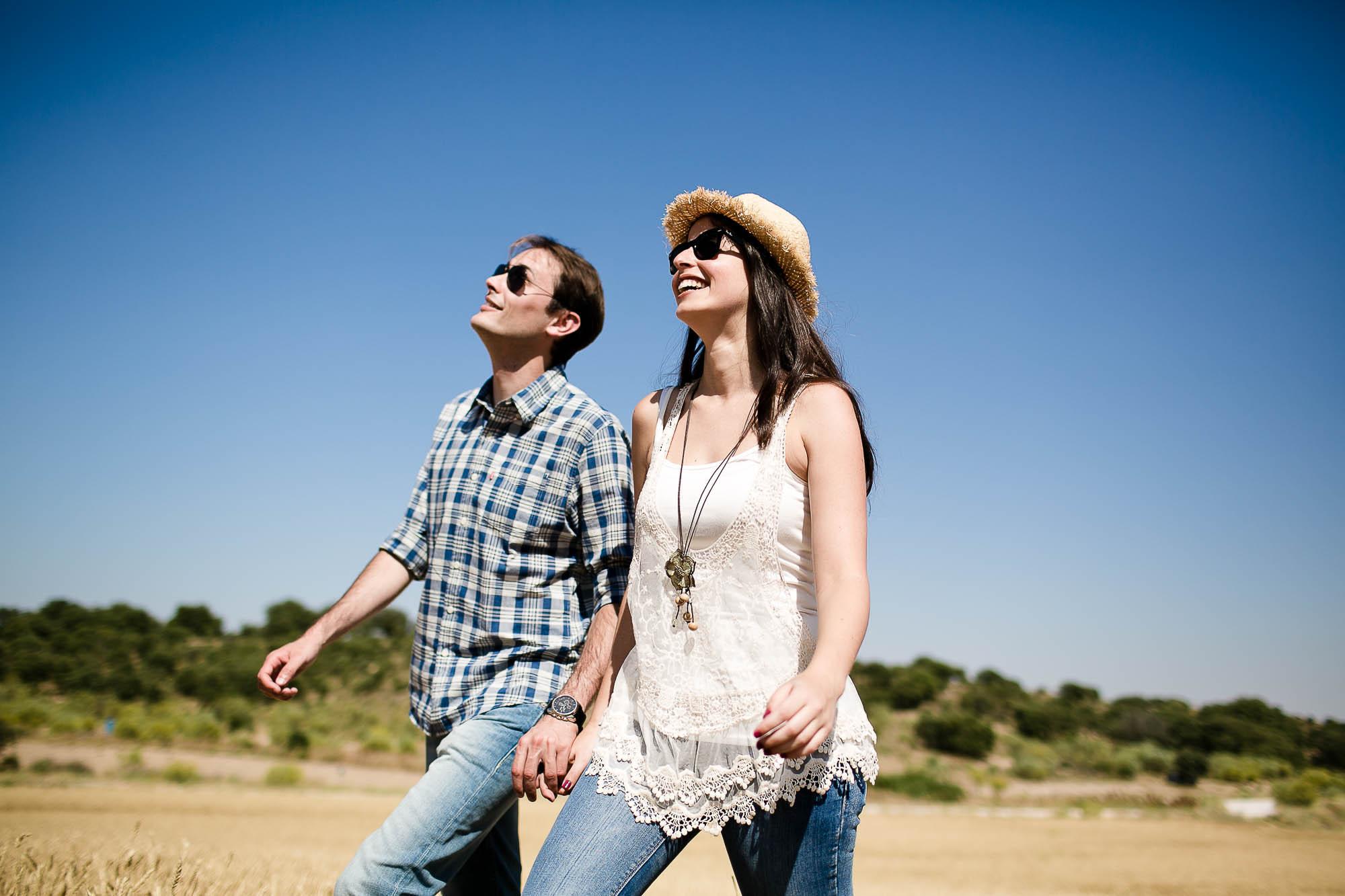 Ella y él pasean cogidos de la mano por le campo en un día soleado