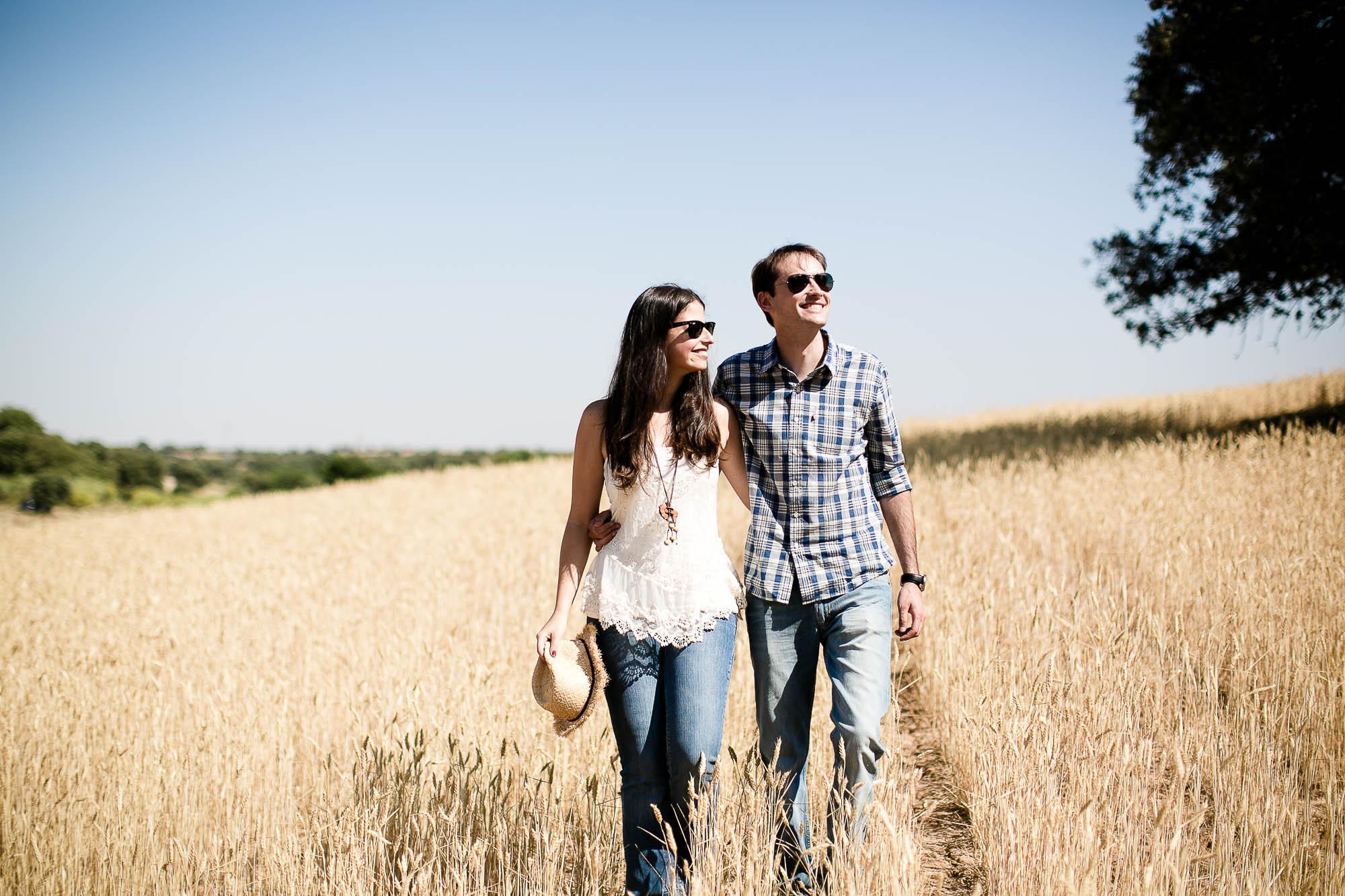 La pareja sonriente pasea abrazada por el campo en un día soleado