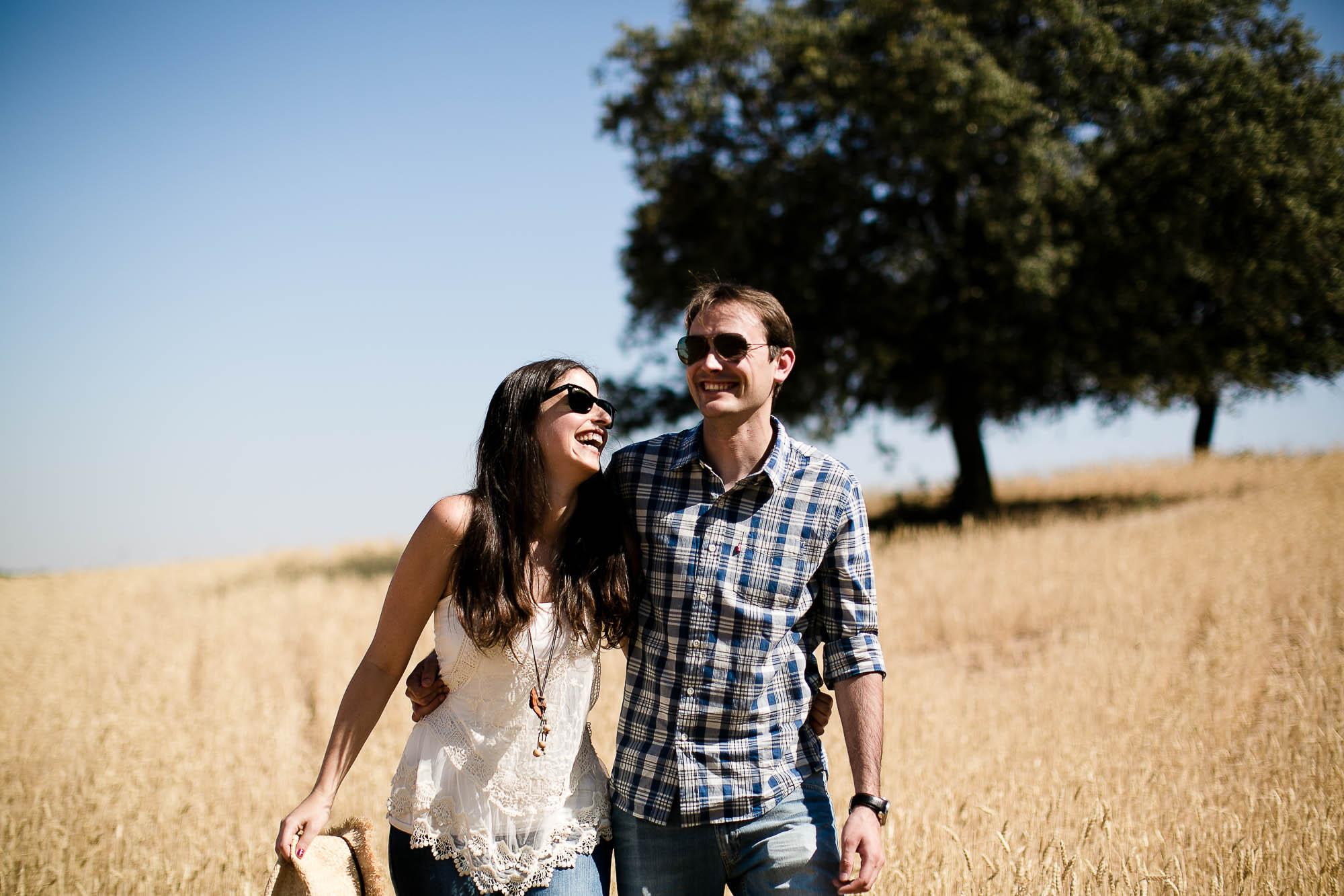 La pareja se abraza y ríen juntos en medio del campo
