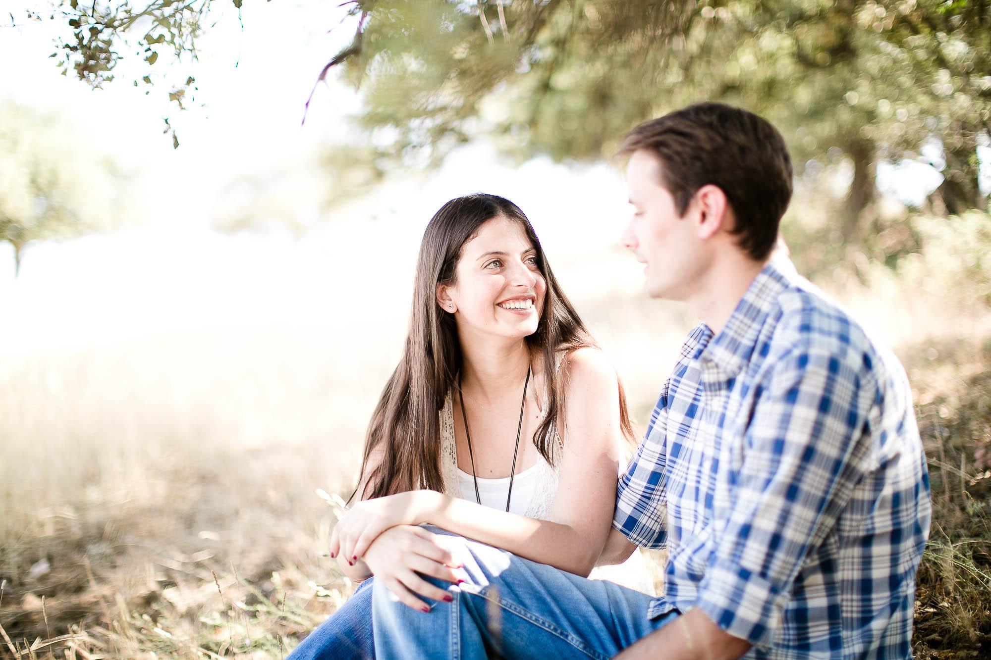 Ella le mira enamorada mientras están sentados en medio del campo