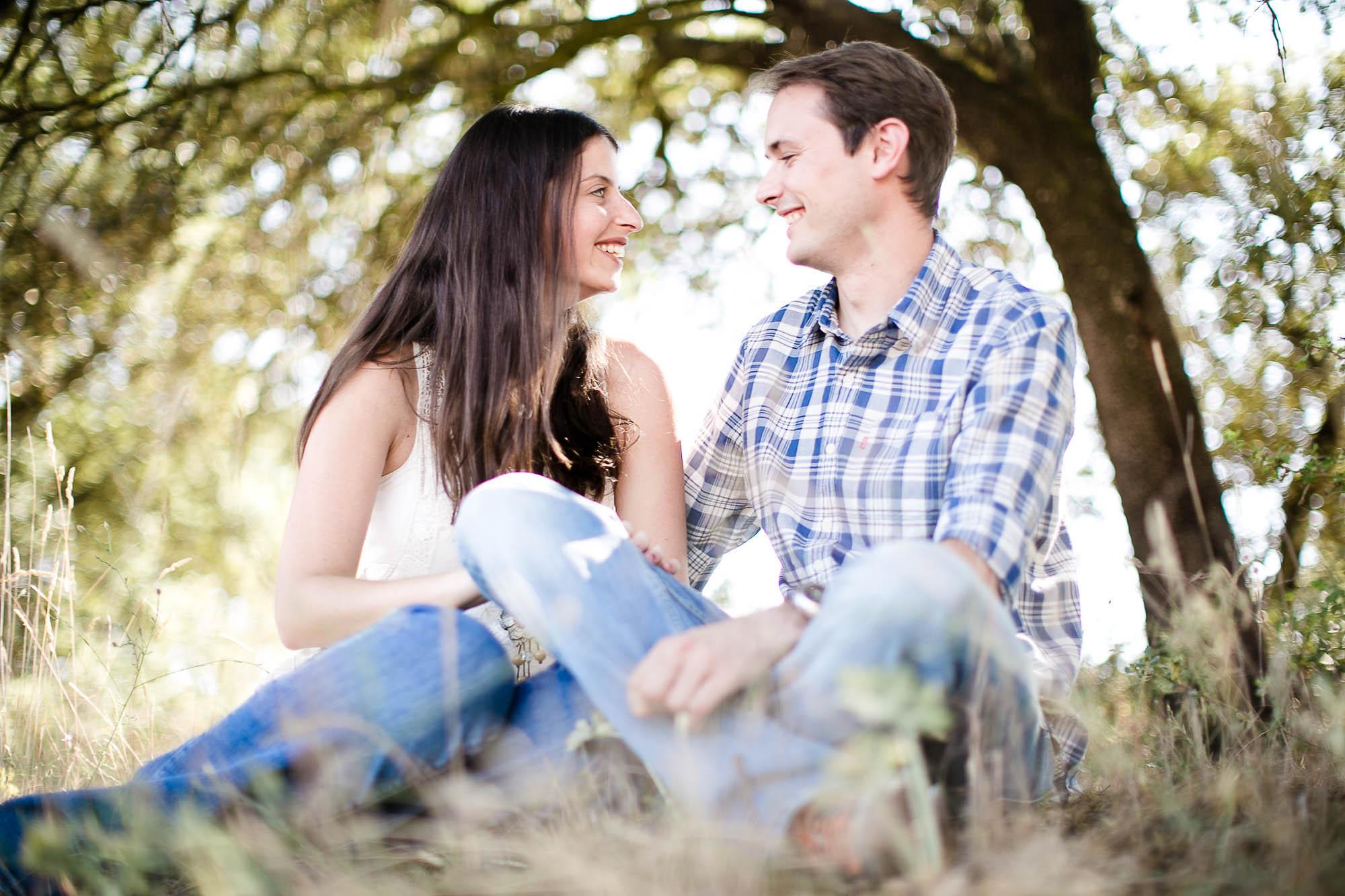 Ellos se miran y ríen juntos sentados bajo un árbol en el campo