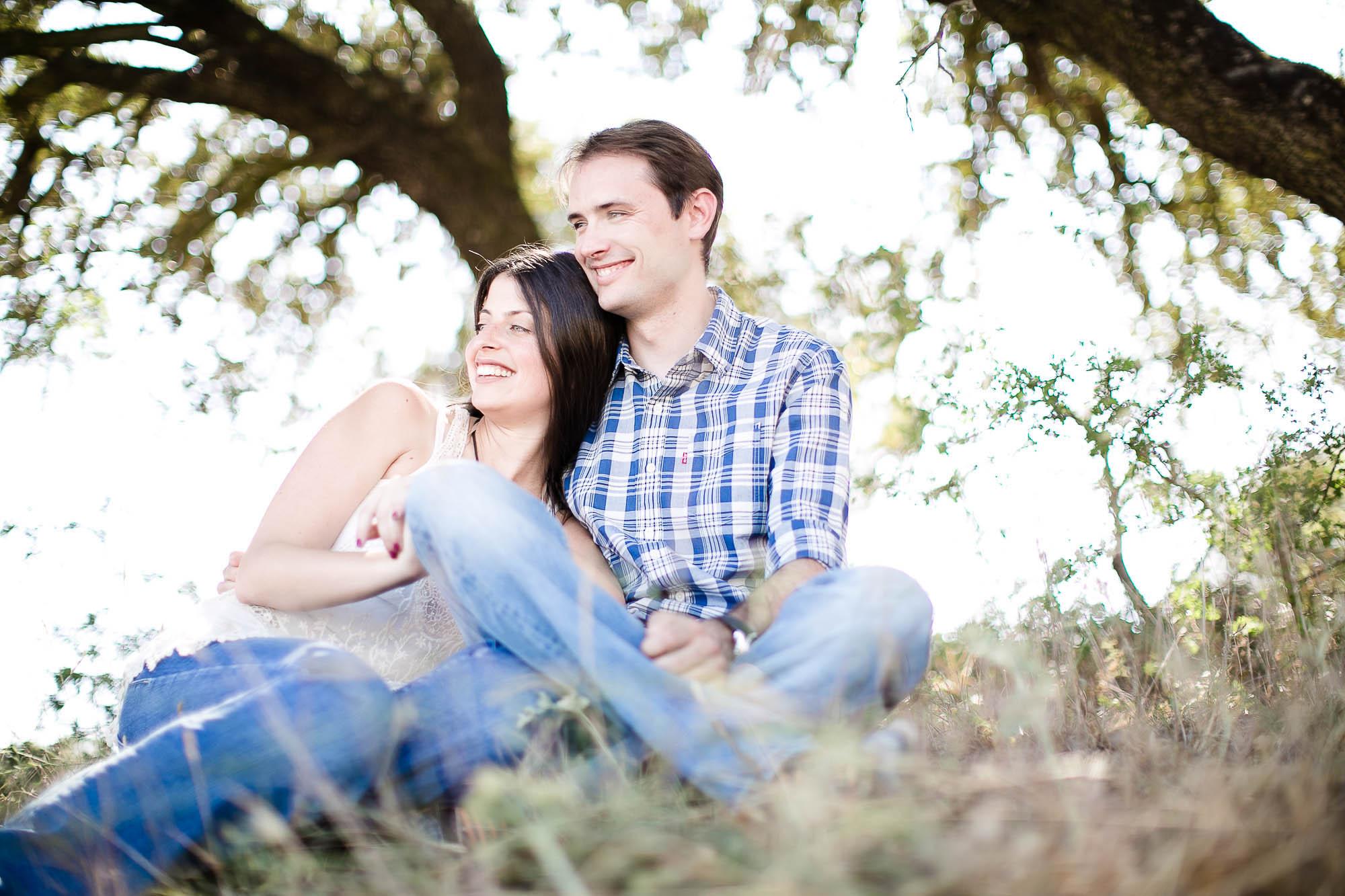 Ellos se abrazan y ríen sentados bajo en árbol