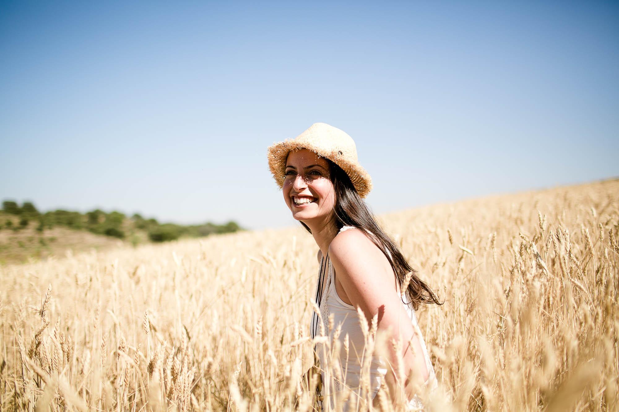 La novia lleva un sombrero de paja y ríe en medio del campo