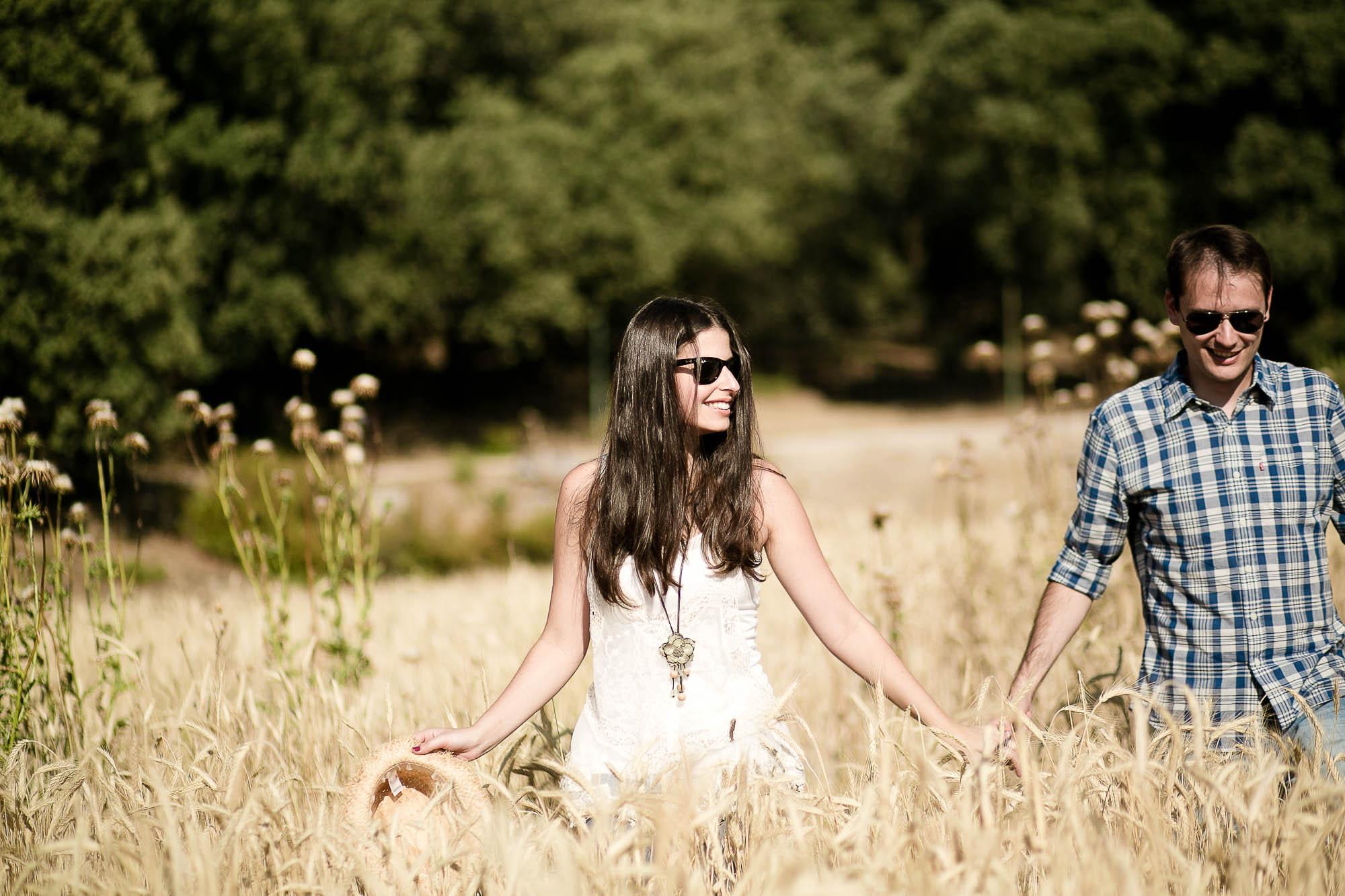 Los novios se cogen de la manos mientras pasean en un día soleado