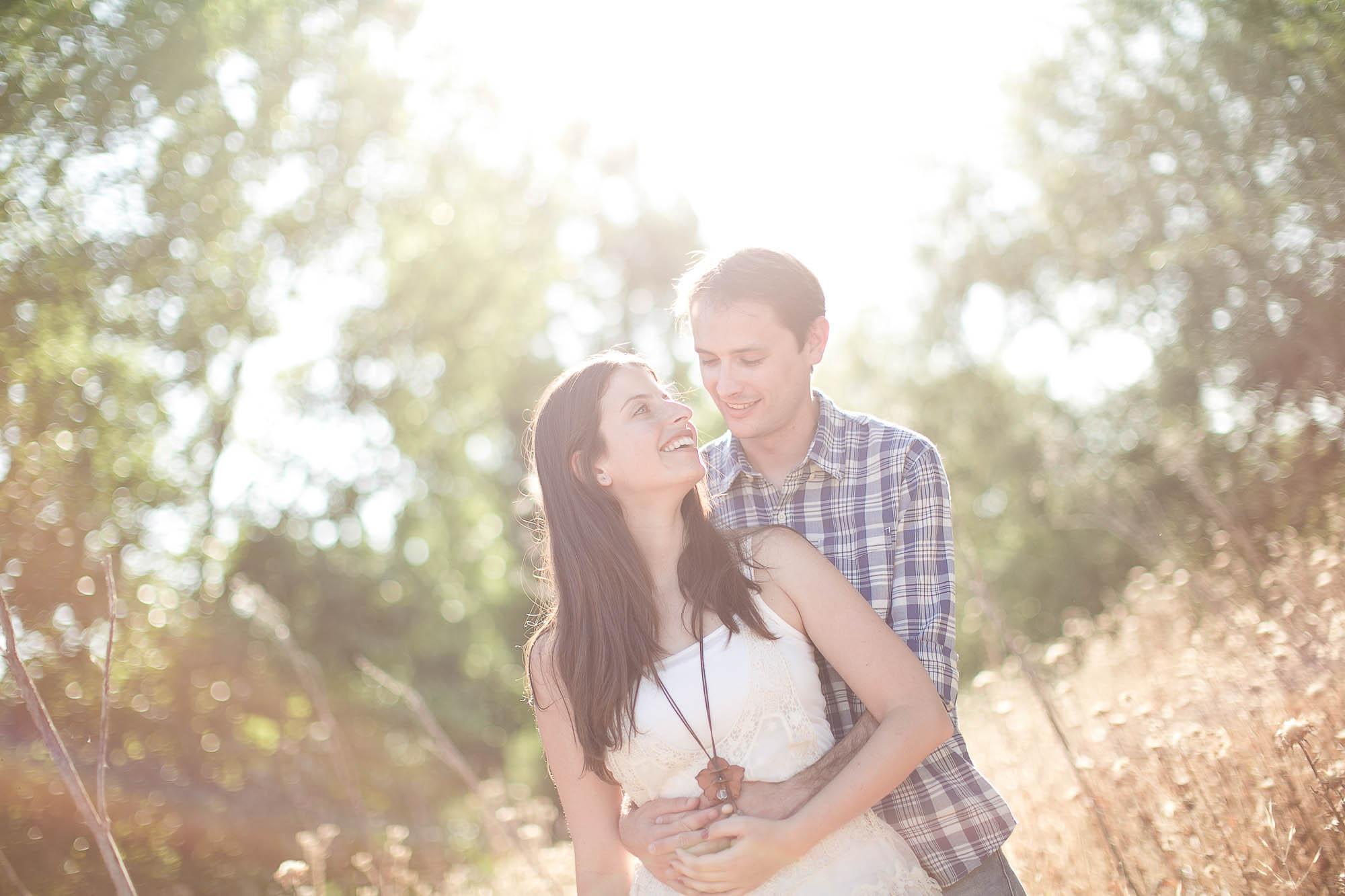 La pareja se abraza bañada por la luz del sol
