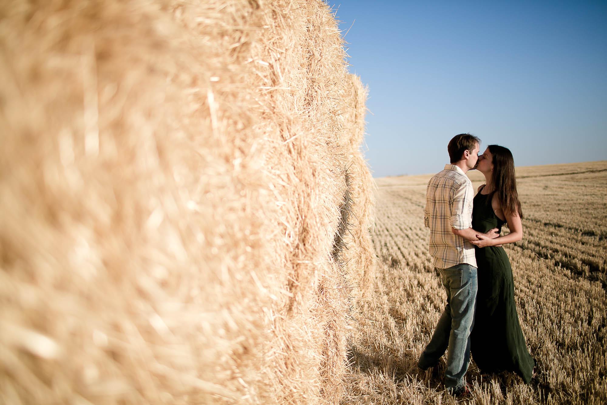 Ellos se besan junto a la montaña de trigo en un día despejado