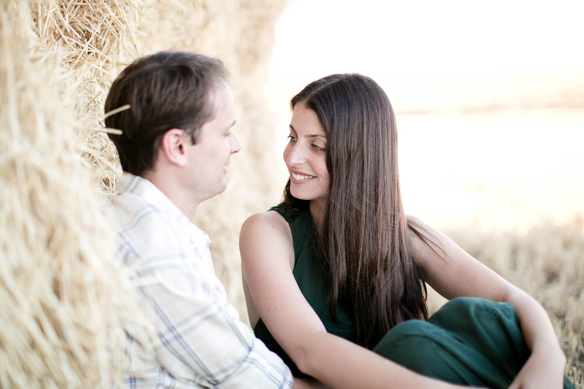 La pareja sentada en el trigal se mira enamorada