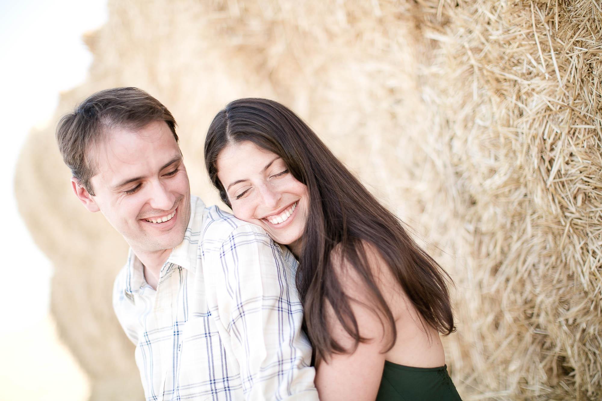 La pareja feliz se abraza junto a la montaña de paja seca