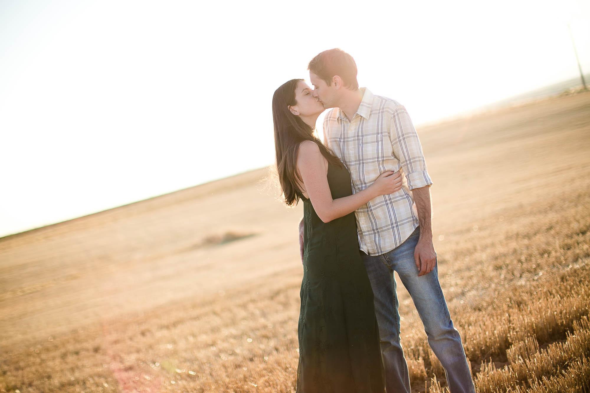 Los novios se abrazan y besan en un atardecer en medio de un campo de trigo
