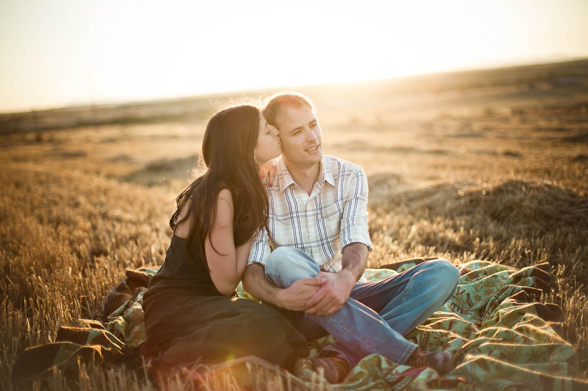 La novia besa al novio sentados en un campo de trigo
