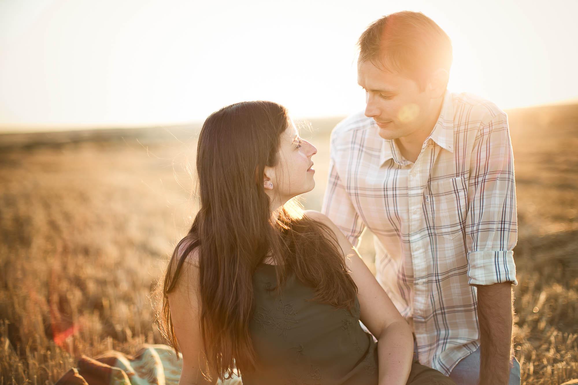 El novio mira a la novia sentados en un campo de trigo