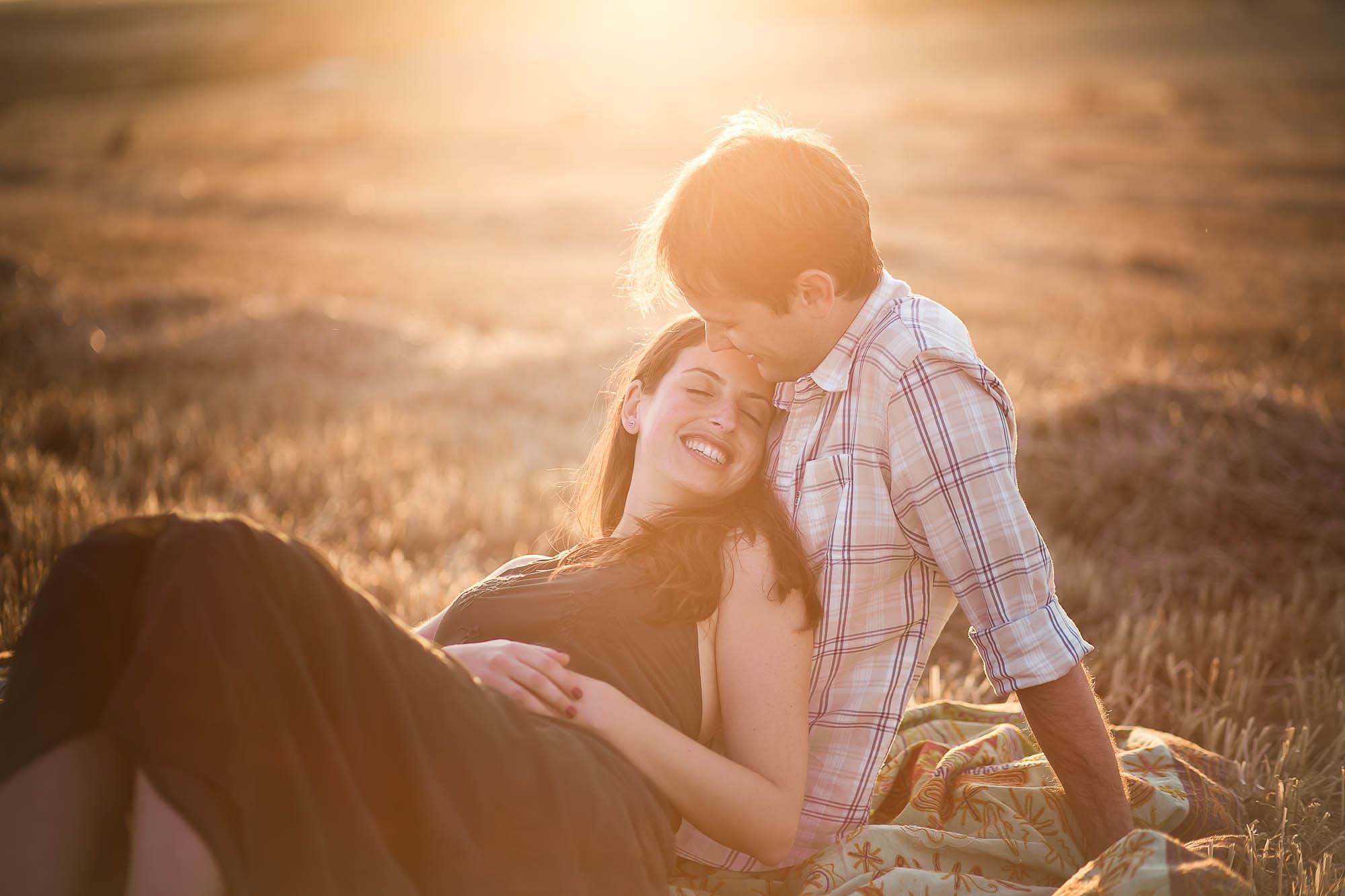 Ella sonríe junto al él sentados en medio del campo