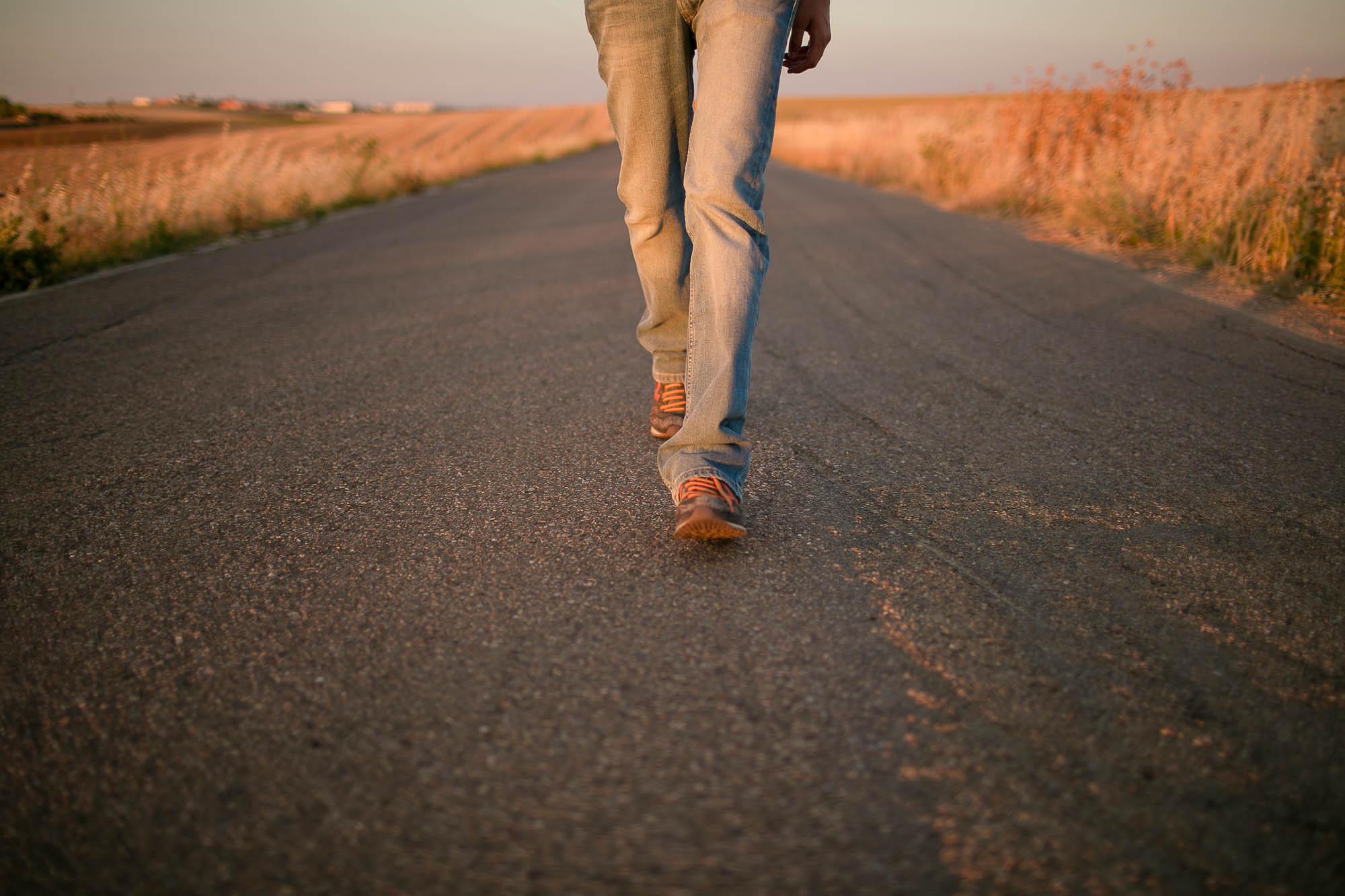 El novio camina por una carretera asfaltada