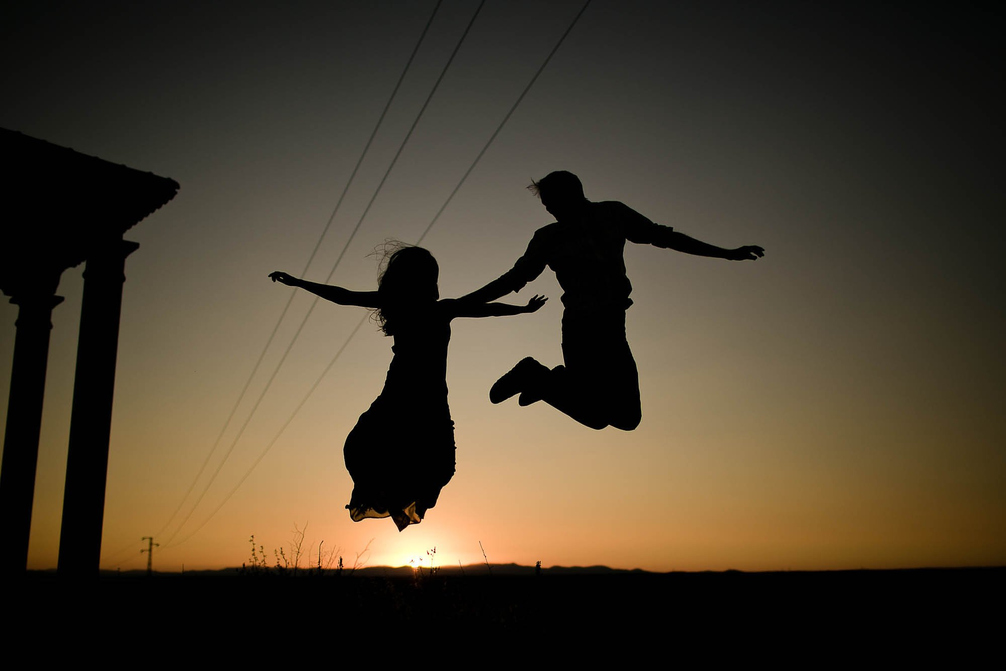 Los novios saltando en medio del atardecer el día de la preboda