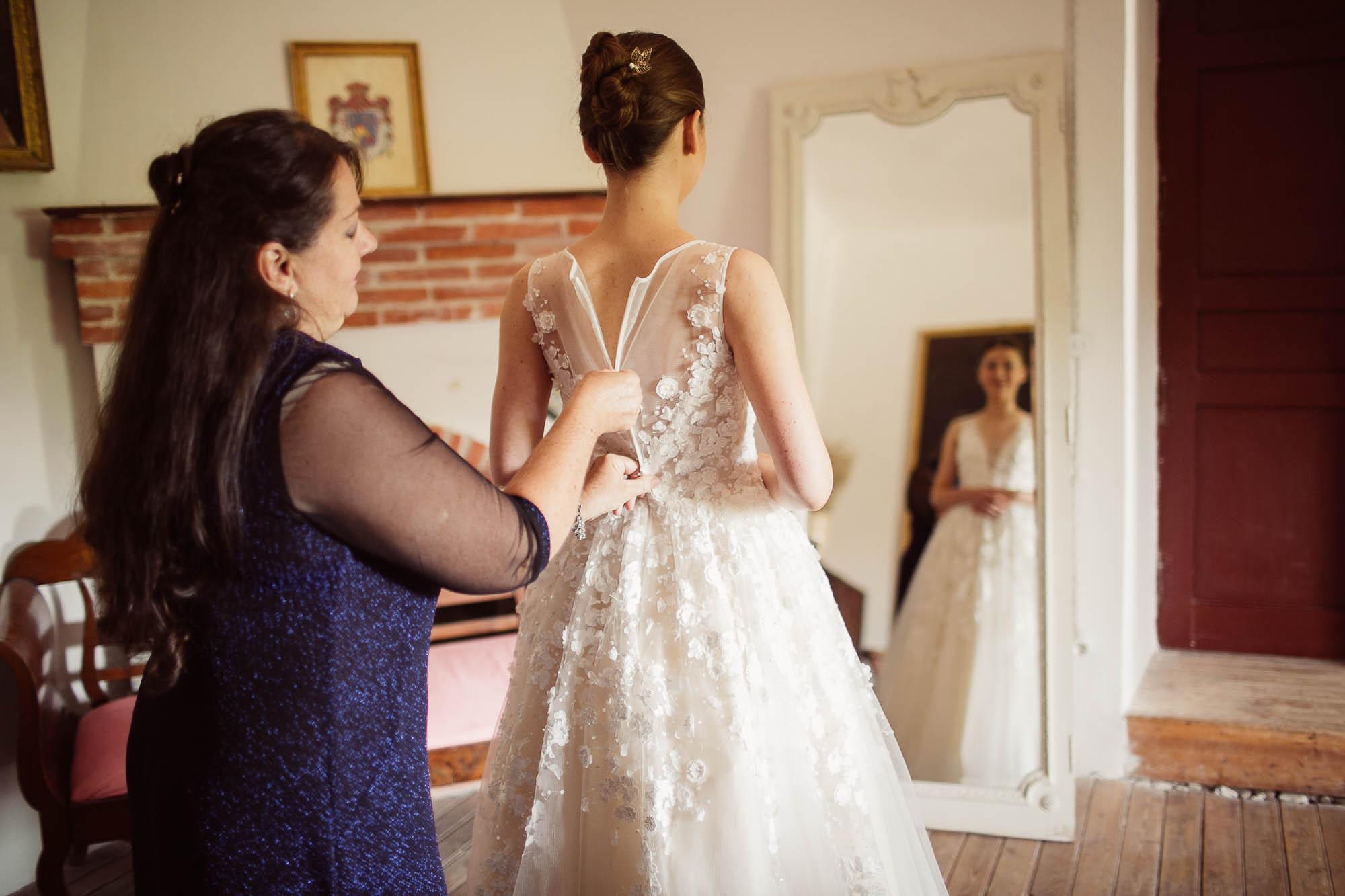 La madre ayuda a cerrar el vestido de la novia