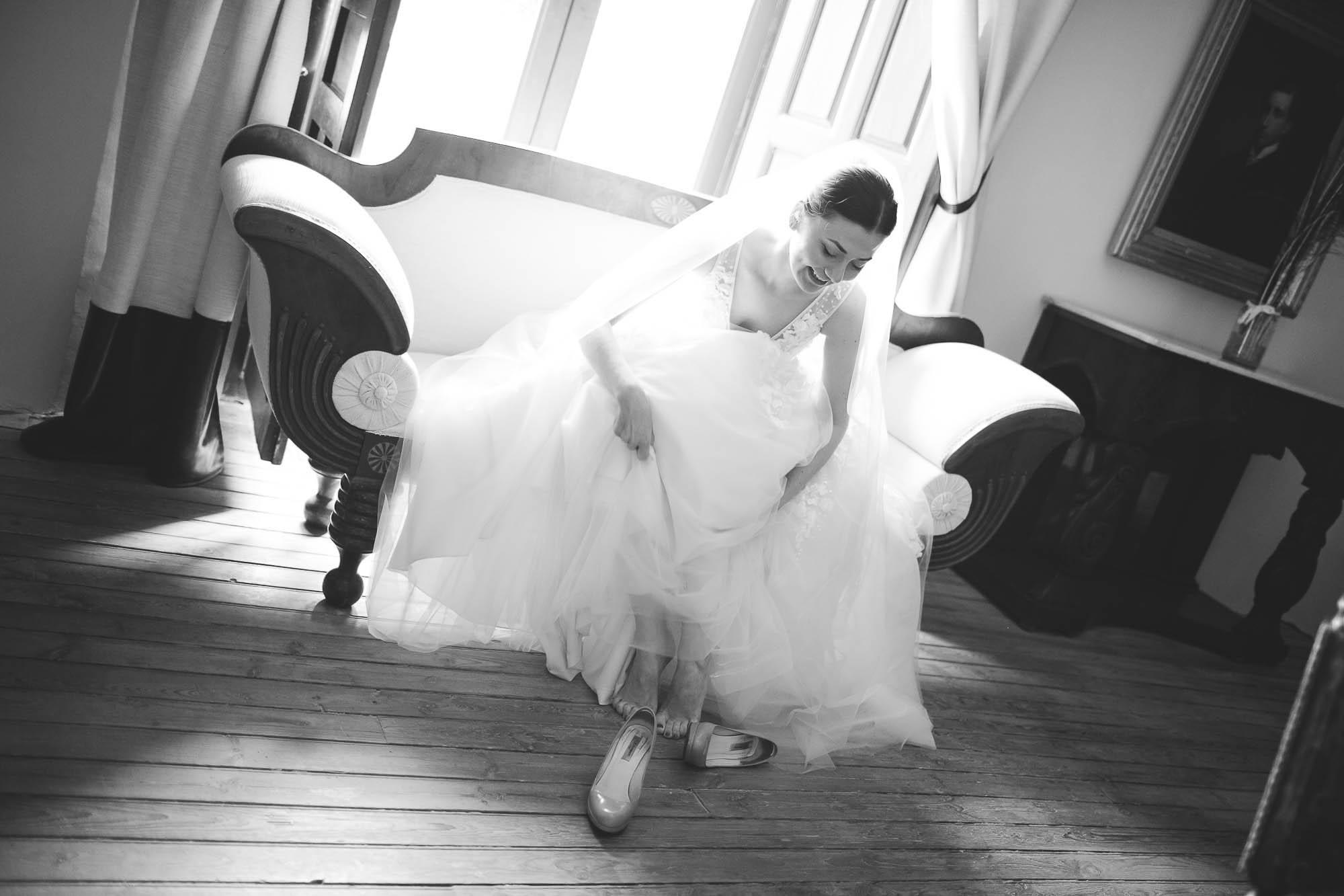 La novia sentada en el sofá se pone los zapatos