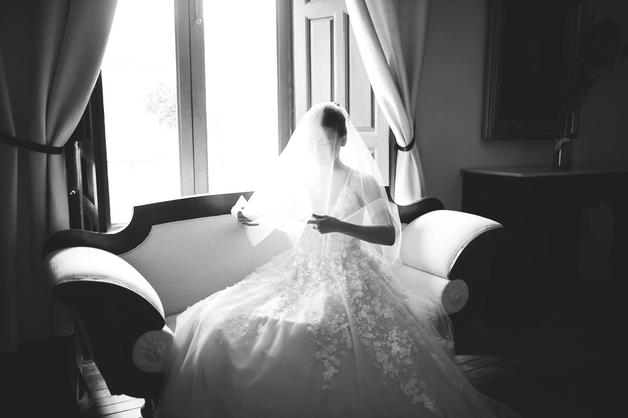 La novia sentada en el Sofá se coloca el velo
