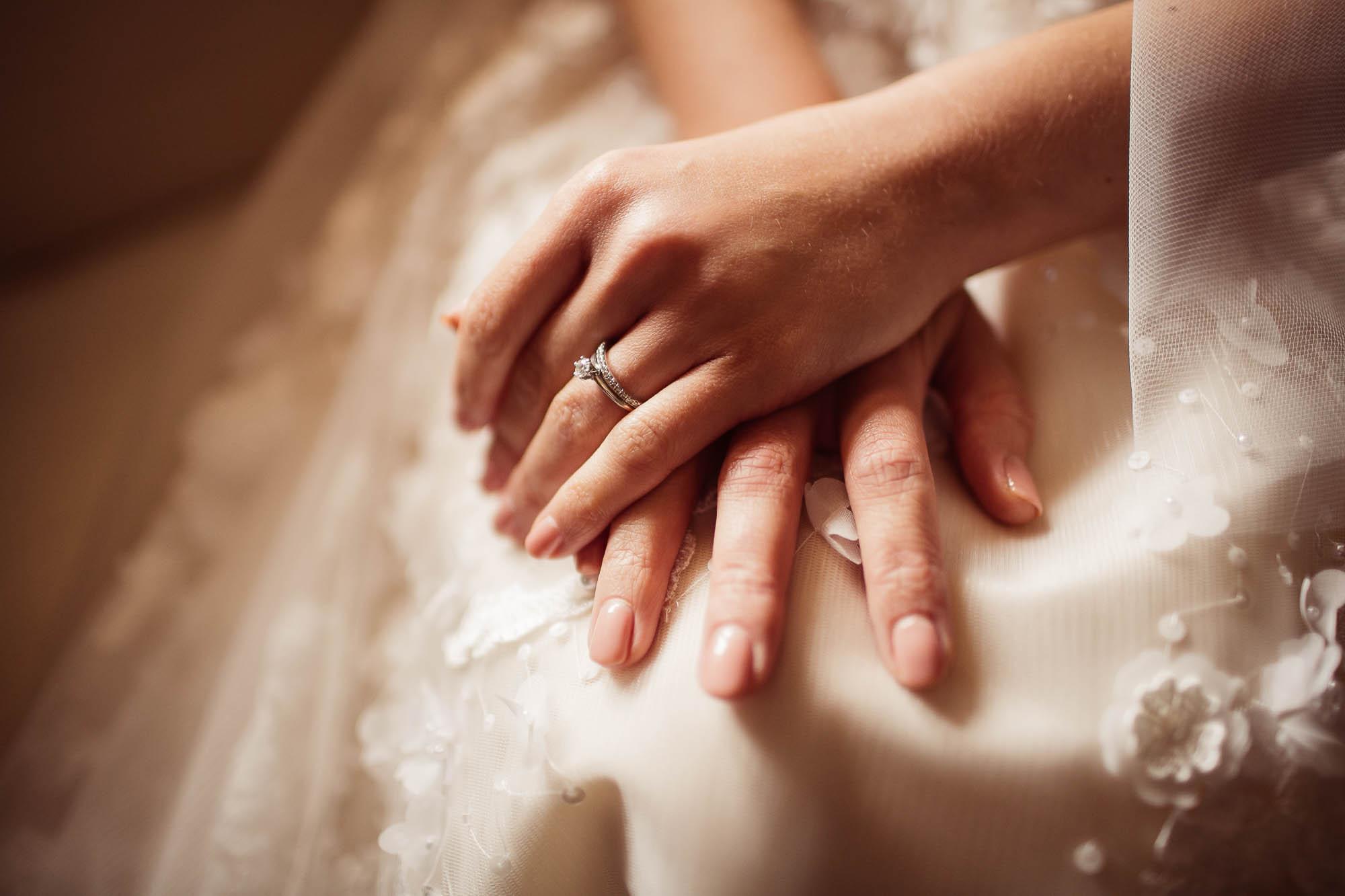 La novia coloca las manos en el regazo con el anillo de compromiso
