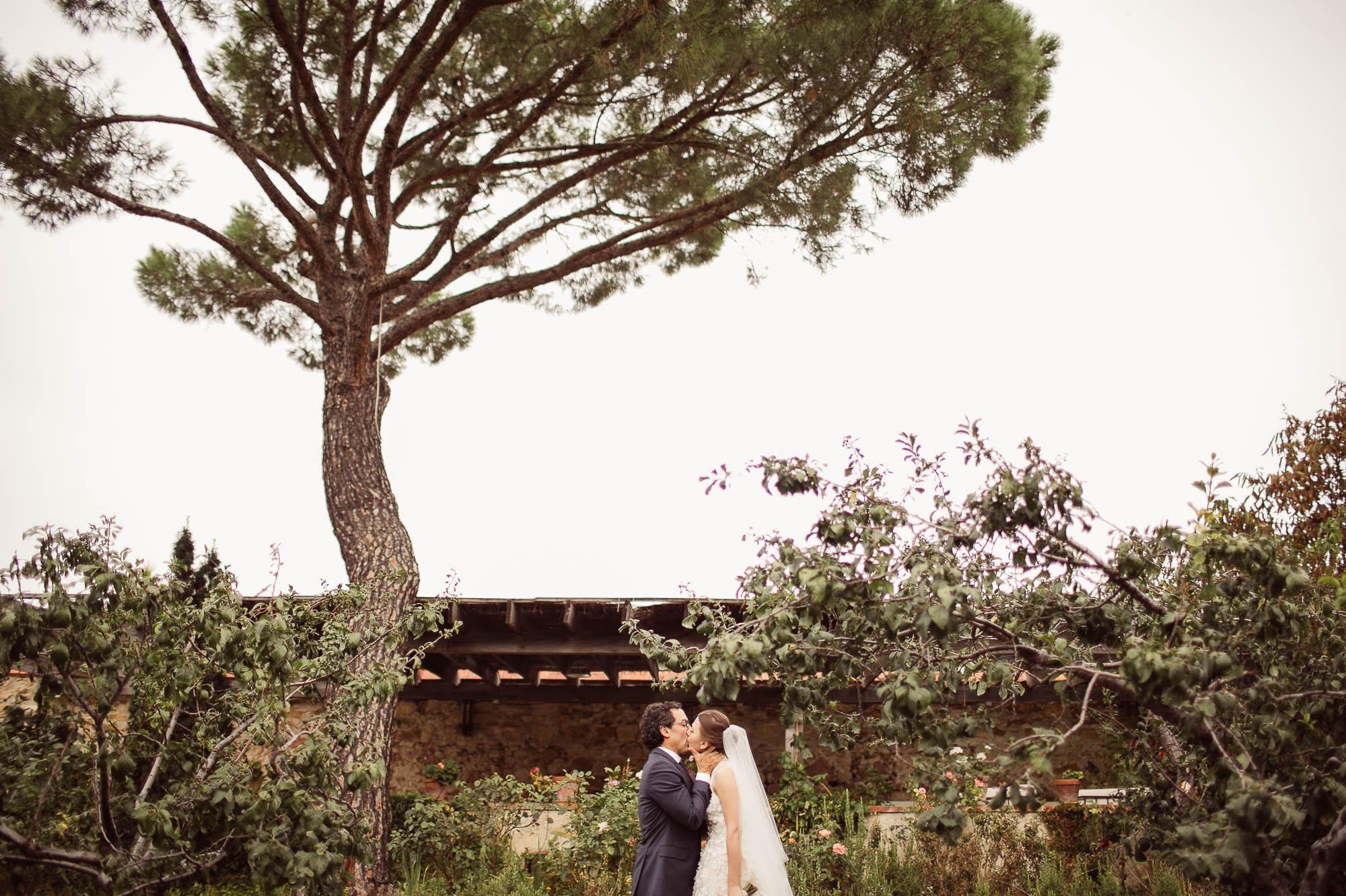 Los novios se besan en el jardín el dia de la boda