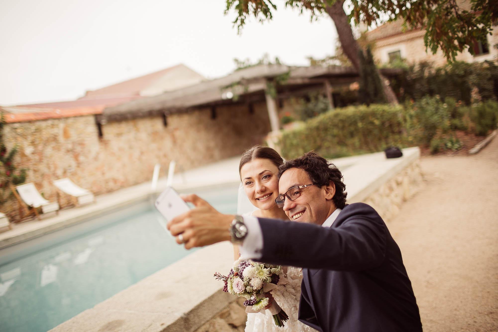 Los novios se hacen un selfie junto a la piscina el dia de la boda