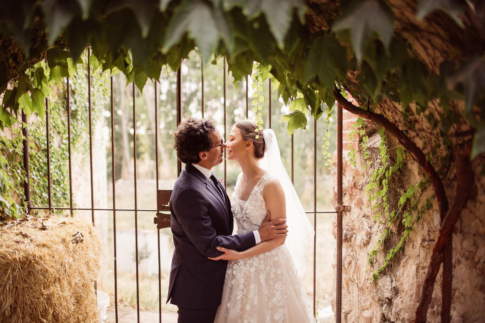 Los novios se besan en el patio el dia de la boda