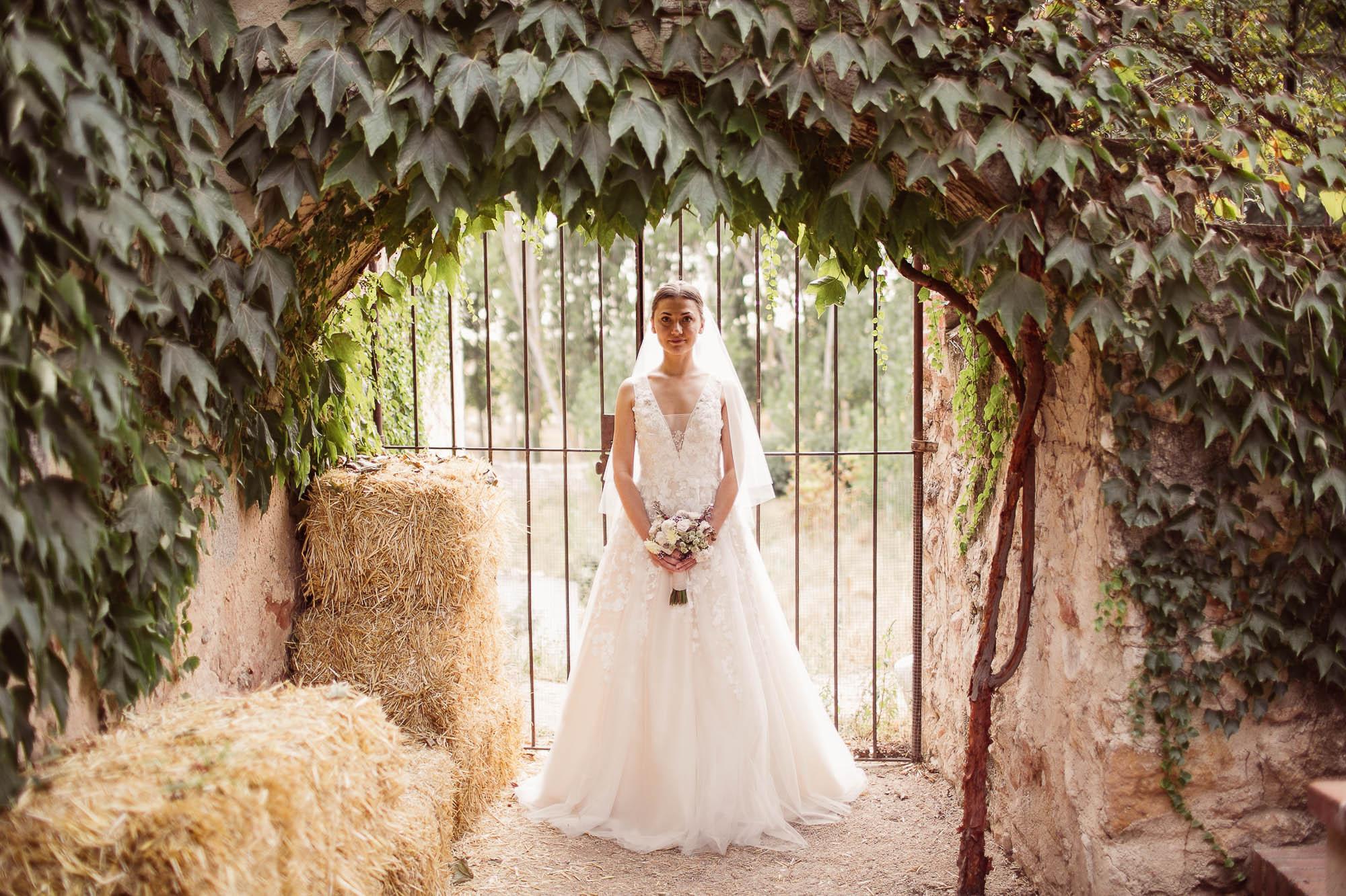 La novia posa en el patio lleno de enredaderas