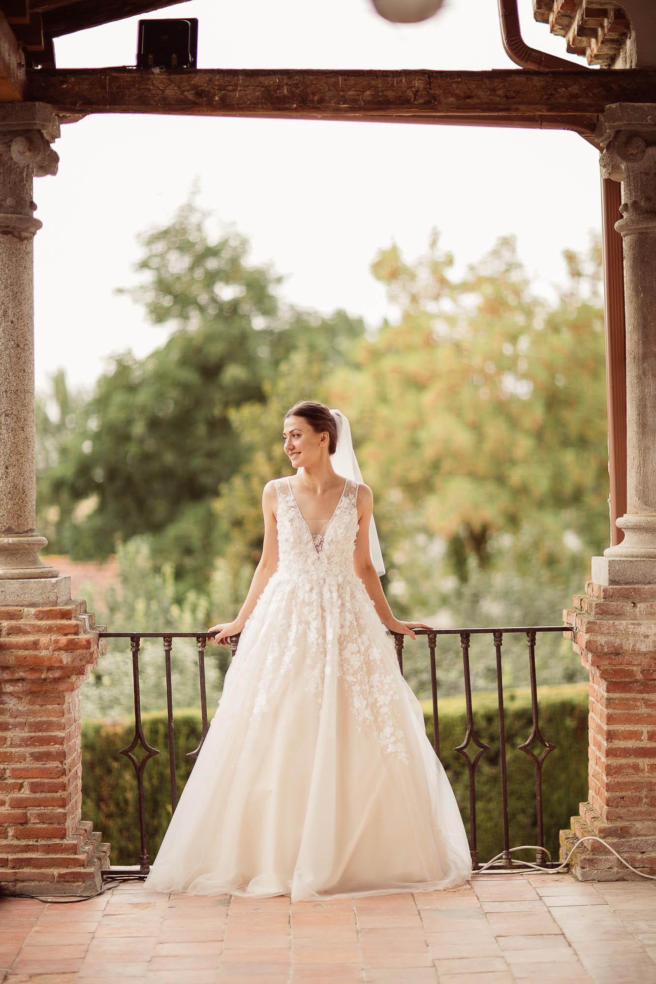 La novia sonríe de pie en el balcón